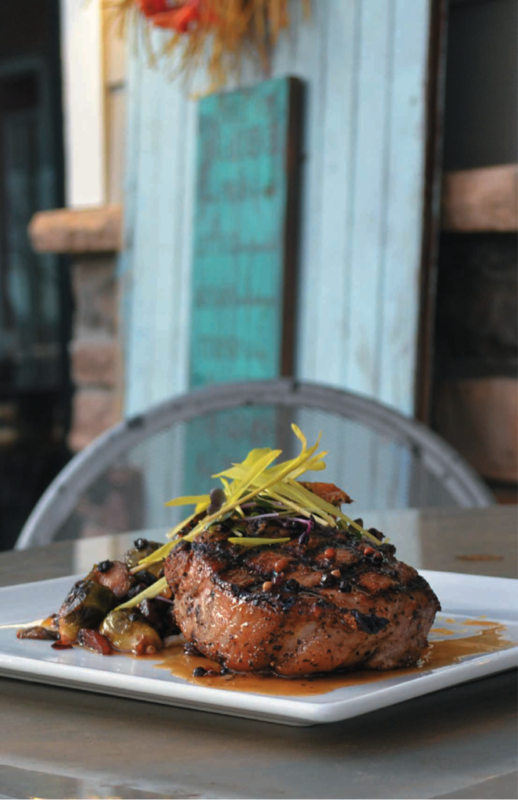Cozy's Pub's Agrodolce Seasoned Bone-In Pork Chop with House Mashed Potatoes Brussel Sprouts Peppercorn Gastrique